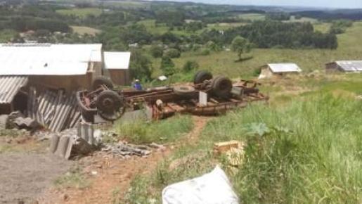 Caminhão atinge casa ao capotar em ribanceira