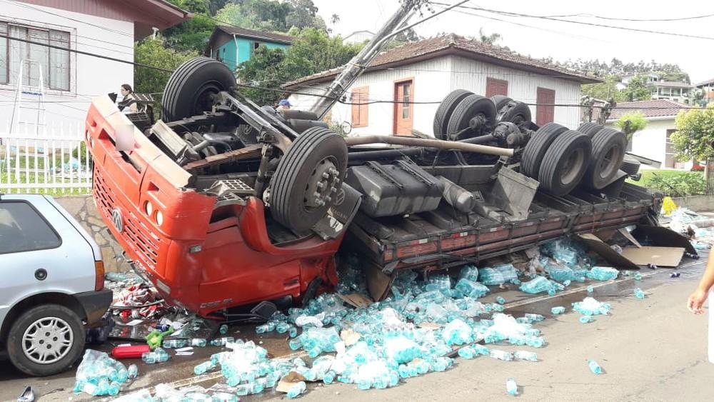 Caminhão bate em muro, tomba e esmaga carro em SC